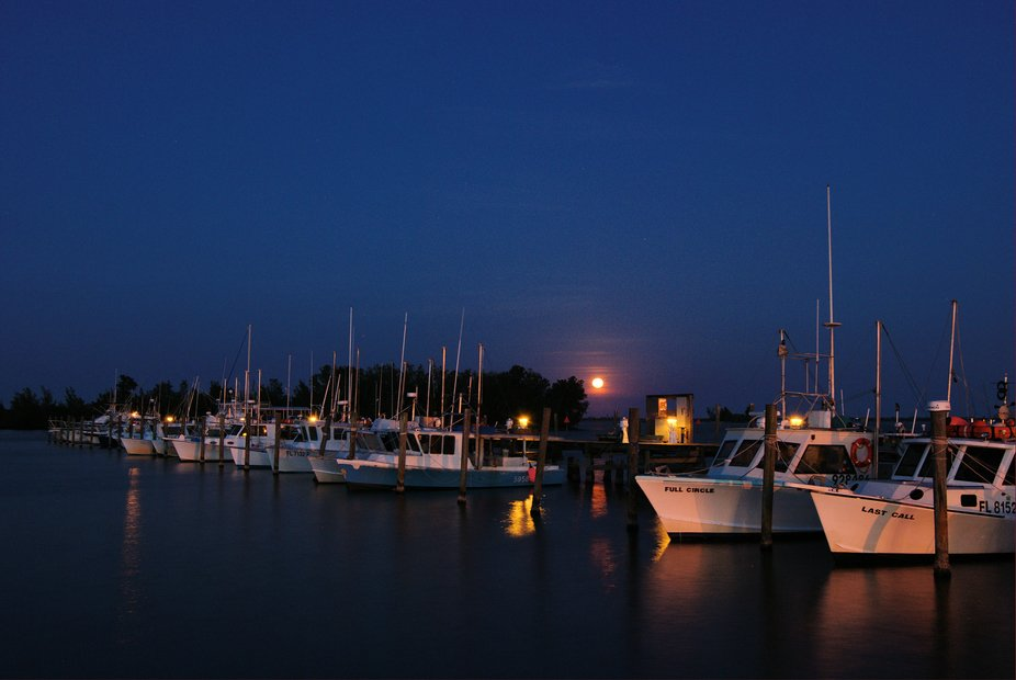A Holy Saturday full moon rises over the fishing fleet in Sebastian, FL