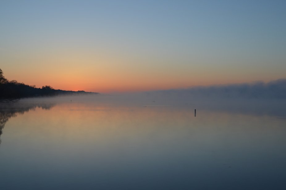 A fog bank over water at sunrise
