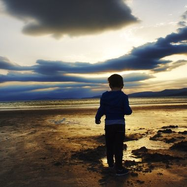 scenic view of child against the ocean and golden sunset