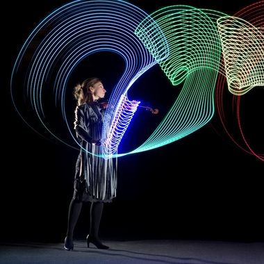 Violinist with her visualised play. An LED strip was taped to the bow, the camera was panned during a long exposure in the dark. Flashes were fired on the second curtain. 