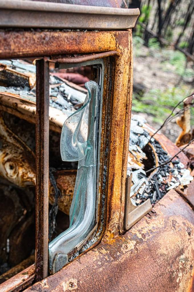 """Taken on a property after the bushfires this cars quarter glass window (FB Holden for the enthusiast) shows how hot the flames  where  – enough to melt glass.  A series of photos to follow from my """"Highway to Hell"""" album. Camera: Nikon D5300 Lens 18.0-140.0mm f/3.5-5.6 Focal Length:40.00 mm, Exposure: 1/200 sec; f/7.1; ISO 400 www.sparrowfarts.com  #Sparrowfartss"""