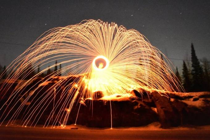 Spinning steel wool at the rock cut on highway with the full moon as backlight