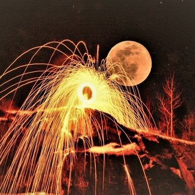 Spinning steel wool with full worm moon in background