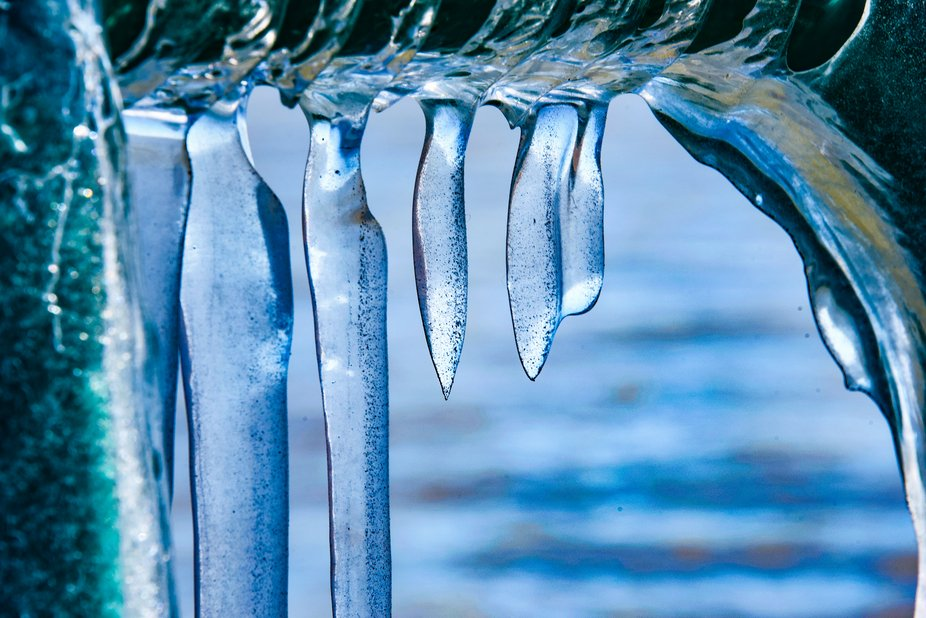 Icicles hanging from the railing on break wall of Lake Michigan. Icy water, icicles, blue sky, al...