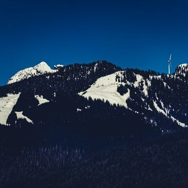 You can see the ski runs of Grouse Mountain and wind turbine