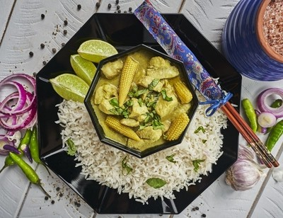 Thai Green curry on a distressed white table top.
