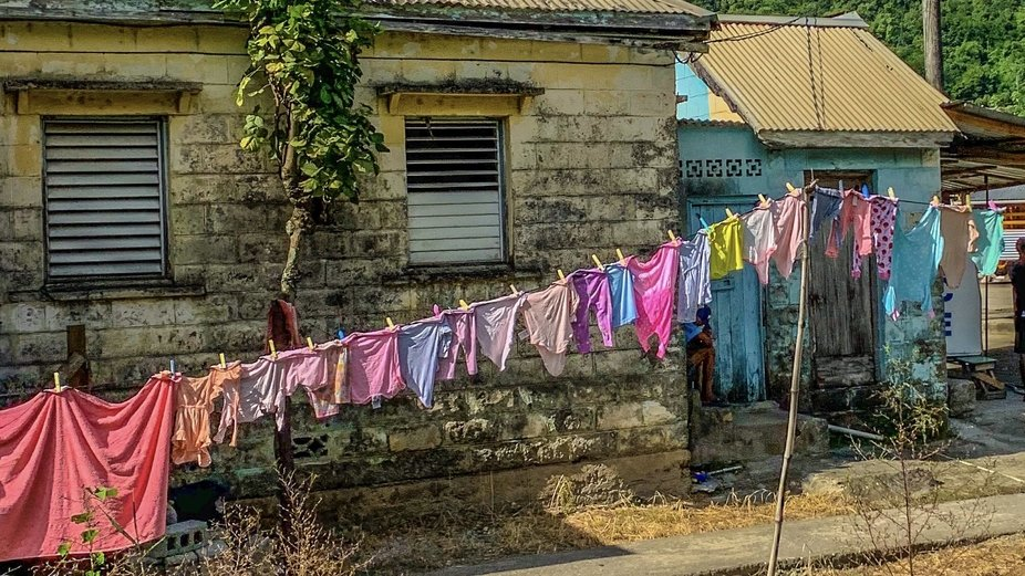 Colorful clothes hang like flags against the backdrop of stone buildings.  This is part of a coll...