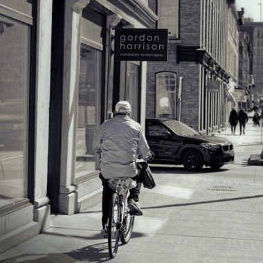 Older man, riding a bicycle on the sidewalk, downtown Ottawa.