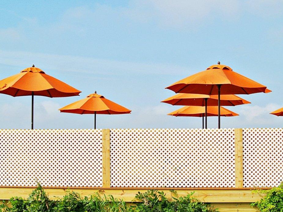 orange umbrellas behind the wall