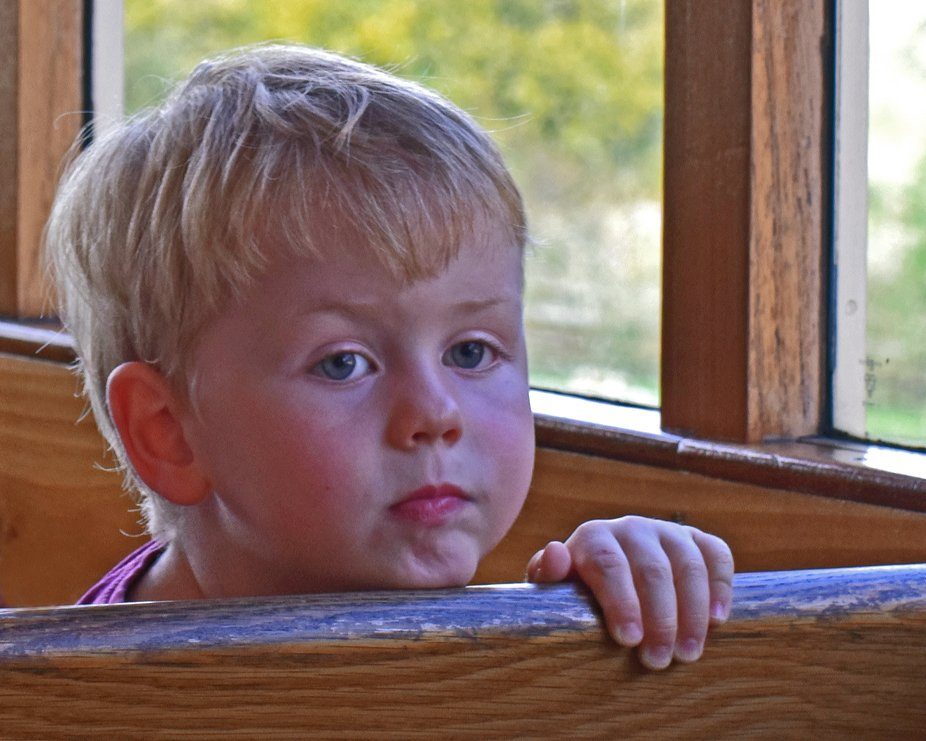 Tired little boy on tram at Beamish museum UK.