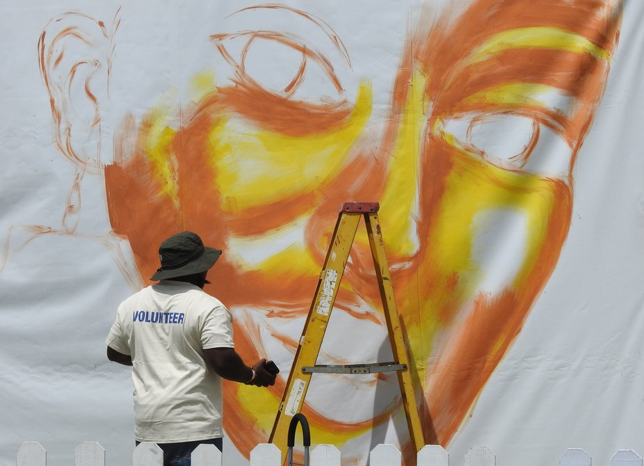 A mural painter just starting on a street side masterpiece painting.  Street art is a very big th...