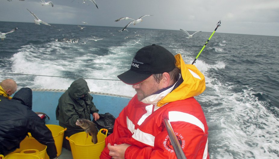 Gutting the fish and holding on. Taken on a fishing trip off Amble in Northumberland UK.