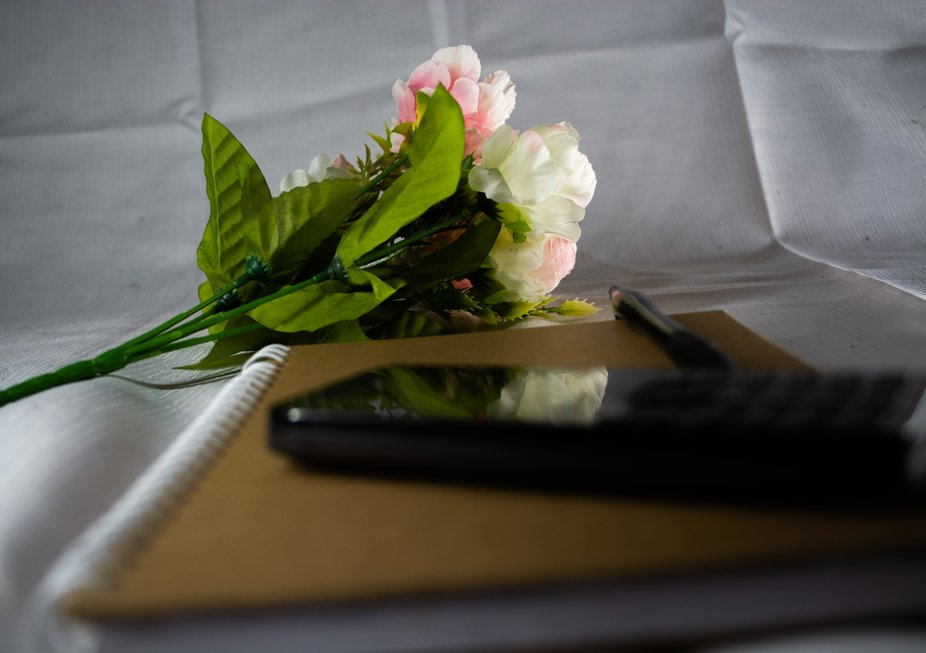 book with phone and flowers