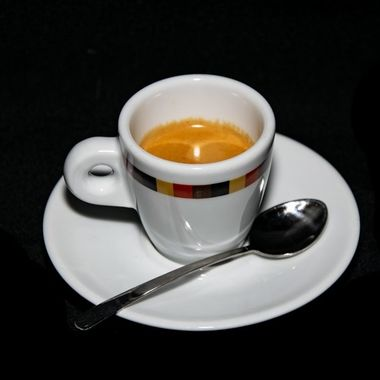 a cup of freshly grounded espresso coffee alongside a plate and spoon