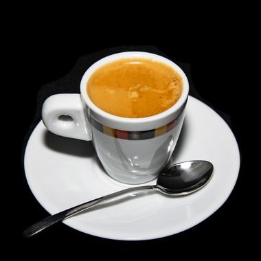 a cup of freshly grounded double espresso coffee alongside a plate and spoon