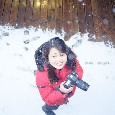 A lady with a camera stands in some snow.
