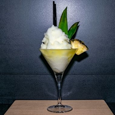 a frozen pina colada fruit cocktail served in a martini glass