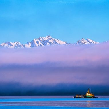 Tug boat with the Olympic Mountains, Mt. Constance from Hood Canal in Washington State.