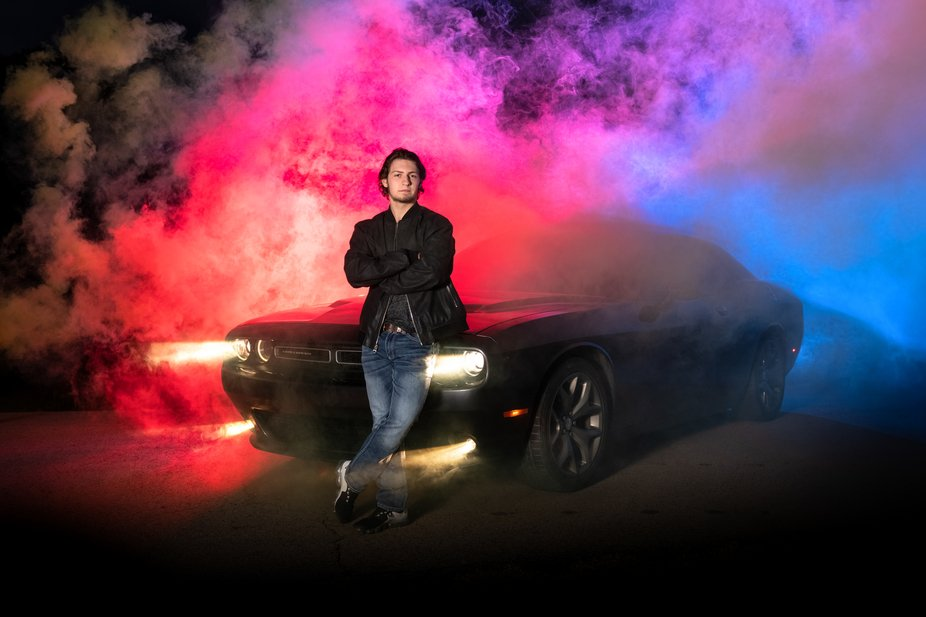 Senior boy with car, smoke bombs and colored lights