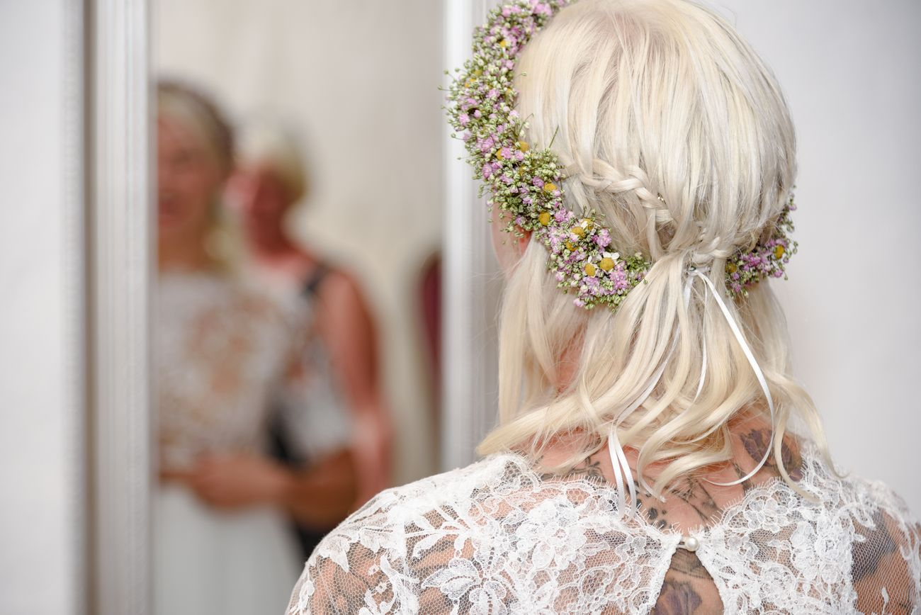 the bride with a bridal hairstyle in a mirror just before the wedding ceremony
