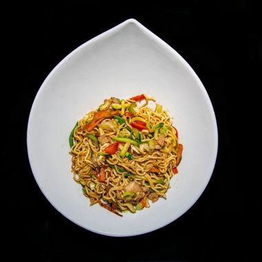 a bowl of spicy wok style chicken and pepper noodles served in a white teardrop bowl