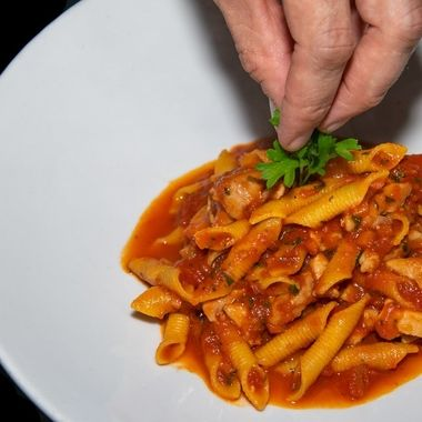 adding the finishing parsley garnish to a freshly made spicy chicken arrabiata pasta dish