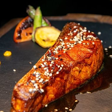 a piece of Canadian salmon cooked in a teriyaki sauce served on a stone and wood plate