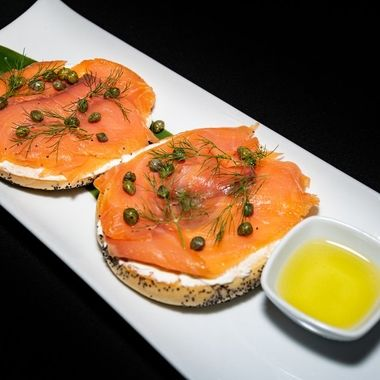 a breakfast bagel filled with smoked salmon and cream cheese spread with garlic oil dip