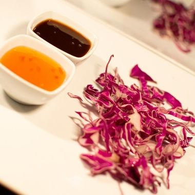 restaurant plate garnish setup of a bed of red cabbage and a selection of teriyaki sauce and hot and sweet sauce