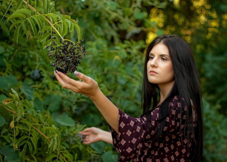 young woman reaching berries in nature with nice nails and hair