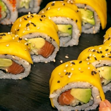 a selection of mango and sesame seed california sushi rolls filled with salmon and avocado