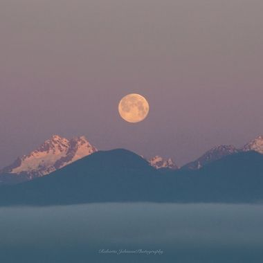 The moon setting upon the Olympic mountains from Hood Canal, Washington, USA