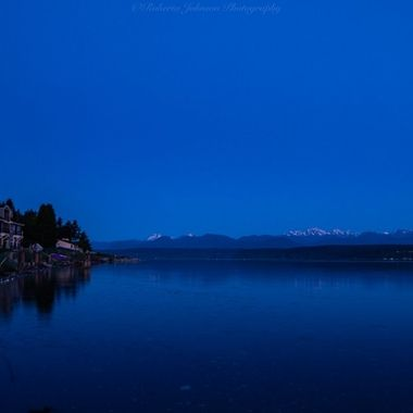 The setting moon with the Olympic mountains. Hood Canal, Washington, USA