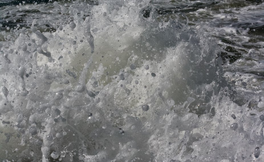 An extreme close up of water spray and droplets as it crashed against shore rocks.