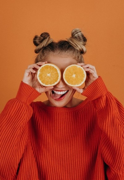 Female model holding two oranges