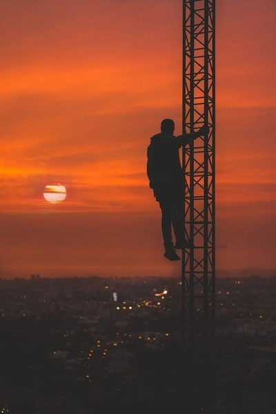 Man holding to an iron tower at sunset