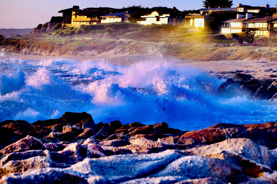 Turbulent Shores, heavy surf brings dramatic waves aglow at sunset from reflected rays of the coastal homes