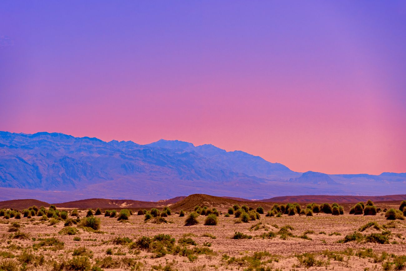 Colorful sunset of purple, blue, red, pinks and oranges in desert with mountains beyond. Death Valley, California.