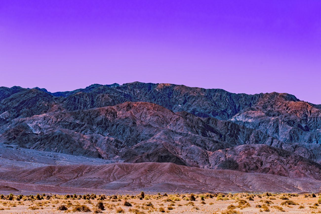Purple sunset over desert mountains.