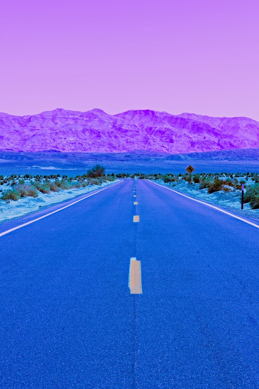 Desert sunset over highway CA 190, light purple sky and mountains turning to blue. Long paved road leadning into desert valley.