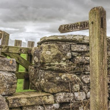 Drystone Wall with wooden stile and footpath signpost