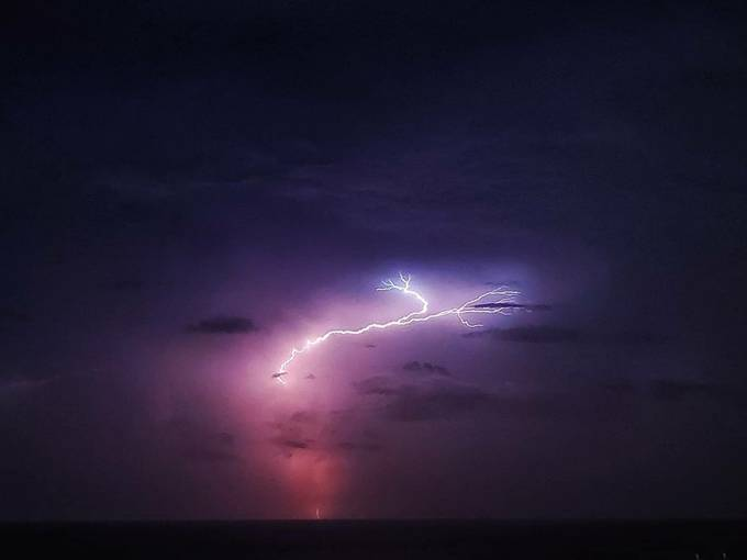 Humid night creating a light show over the ocean in Pompano, Florida