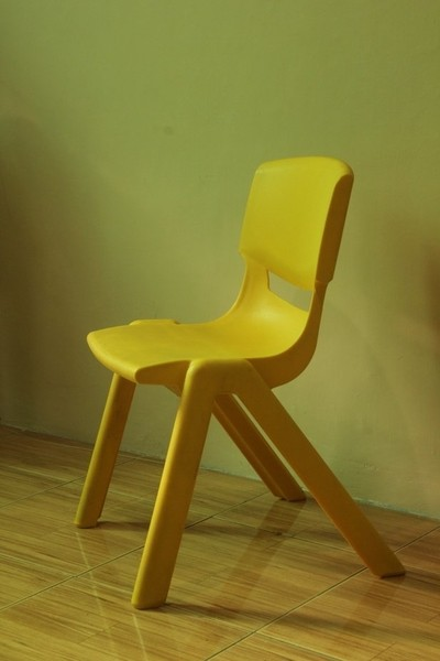 A small yellow chair in the bedroom.