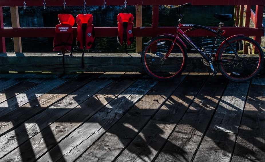 At the side of the wharf the sun back lights the red lifejackets and casts shadows. I removed som...