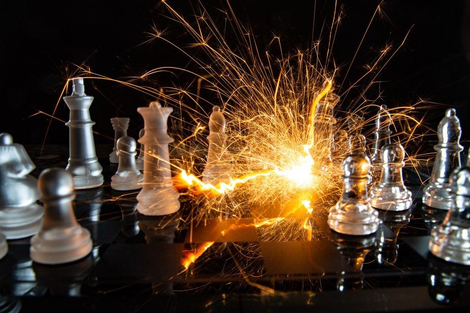 Glass chess set, sparkler, black backdrop