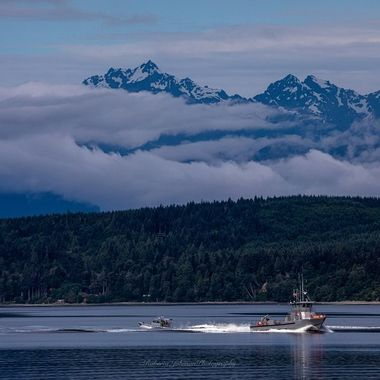 Two Coast guard boats doing a cross over with the Olympic Mountains, Mt. Constance as a back drop.