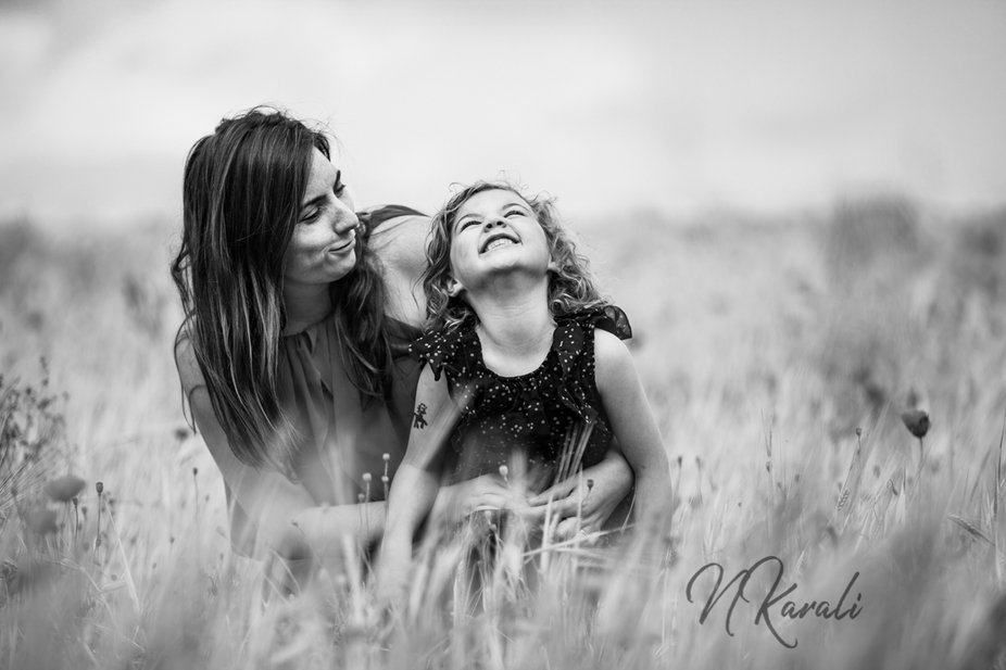 """A happy daughter sitting at mum""""s lap. A picture full of emotions. Shows the love of mum..."""