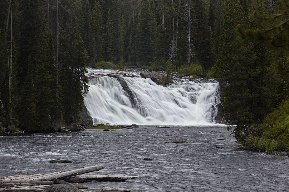 Lewis Falls lies in the southern part of Yellowstone National Park about 30 miles north of the Gr...