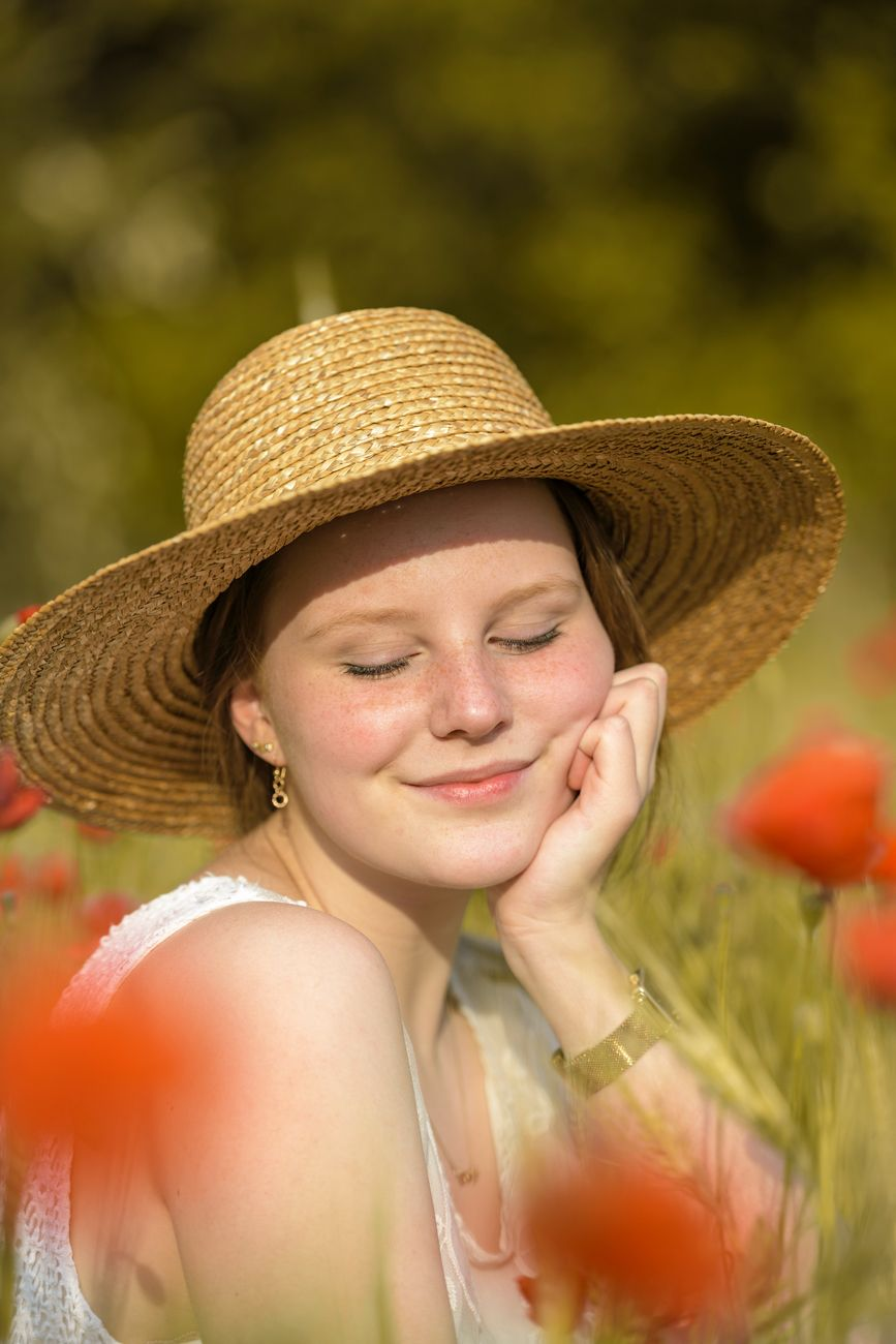 Young girl likes to site in a field of poppies
