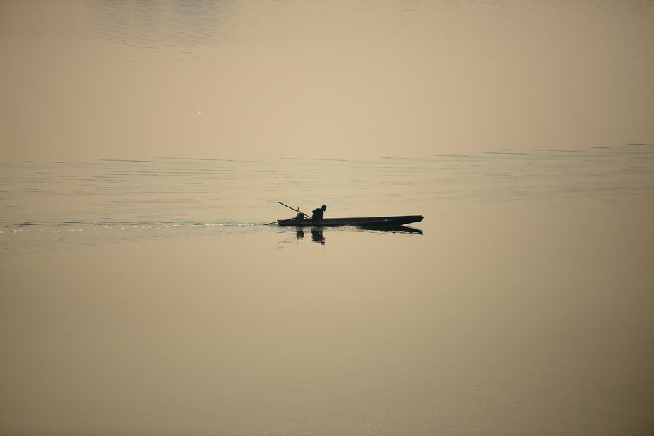 A lonely fisherman on his boat slowly going down the Mekong river in the northern Laos at sunset.